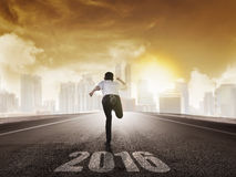 Back view of business man running with 2016 number Stock Photo