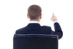 Back view of business man sitting on office chair and pointing a Royalty Free Stock Photo