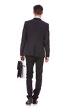 Back view of a business man standing. And holding a briefcase , looking away Royalty Free Stock Images