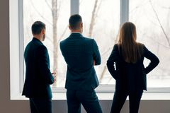 Back view of business people talking during the coffee break stand near the window in office royalty free stock photography