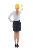 Back view of business woman in builder helmet pointing at someth Royalty Free Stock Image