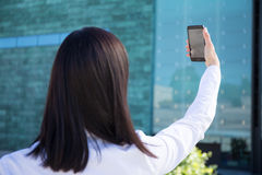 Back view of business woman making selfie photo on smartphone Royalty Free Stock Image