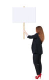 Back view business woman showing sign board. Young redhead girl holds information plate. Rear view people collection. backside view of person. Isolated over Stock Photo