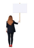 Back view business woman showing sign board. Young redhead girl holds information plate. Rear view people collection. backside view of person. Isolated over Royalty Free Stock Image