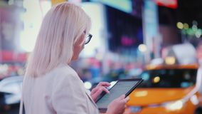 Back view: Business woman uses tablet on busy Times Square in New York. The famous yellow cabs are passing by - the. Business woman uses a tablet on busy Times royalty free stock photo