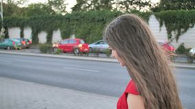 Back view woman walking on the street in modern urban city. Female with brown hair walks in the morning. slow motion. Back view business woman walking on the stock video footage