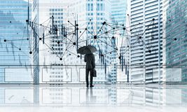 Elegant businessman standing with back and looking at modern business cityscape. Mixed media royalty free stock photo