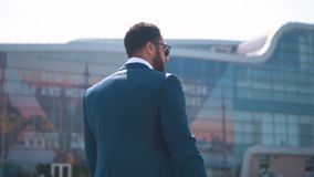 Businessman Carying Case. Back view of businessman in blue suit carying black trip case before modern building of airport, outdoor slowmotion stock footage