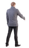 Back view of businessman in coat reaches out to shake hands. Stock Photo