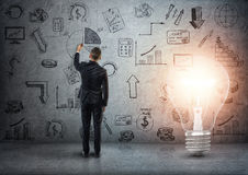 Back view of a businessman drawing business doodles on concrete wall with big glowing light bulb beside him. Ideas and concepts. Creativity and inspiration Stock Images