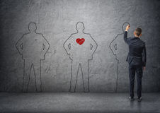 Back view of a businessman drawing men's silhouettes on concrete wall. The middle one with red heart in its chest. Stock Images