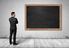 Back view businessman full body standing front of black chalkboard in interior design. Back view of a businessman full body standing in front of a black Stock Photography