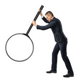 Back view of a businessman holding big magnifying glass in his outstretched arm isolated on white background Royalty Free Stock Photography