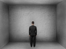 Back view of businessman inside empty concrete room Stock Image