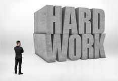 Back view of a businessman looking at big concrete 3D words 'hard work', isolated on white background Royalty Free Stock Images