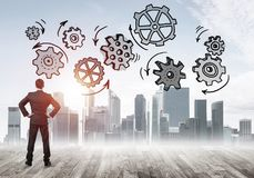 Cogwheel engine drawn on screen as symbol for teamwork and coope. Back view of businessman looking at modern city and drawn gear mechanism Stock Photography