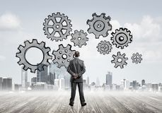 Cogwheel engine drawn on screen as symbol for teamwork and coope. Back view of businessman looking at modern city and drawn gear mechanism Stock Photos