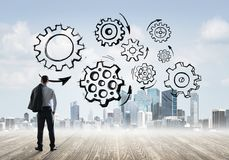 Cogwheel engine drawn on screen as symbol for teamwork and cooperation. Back view of businessman looking at modern city and drawn gear mechanism Royalty Free Stock Images