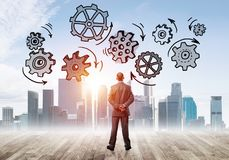Cogwheel engine drawn on screen as symbol for teamwork and cooperation. Back view of businessman looking at modern city and drawn gear mechanism Royalty Free Stock Photography