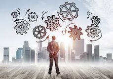 Cogwheel engine drawn on screen as symbol for teamwork and coope. Back view of businessman looking at modern city and drawn gear mechanism Royalty Free Stock Photo