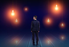 Back view of a businessman looking upwards at light bulbs glowing in the dark stock photo
