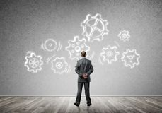 Cogwheel engine drawn on concrete wall as symbol for teamwork and cooperation. Back view of businessman looking at wall with drawn gear mechanism Stock Photo