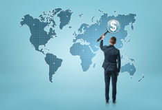 Back view of a businessman looking at world map through magnifying glass and seeing dollar sigh Stock Photography