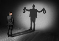 Back view of businessman looks to his shadow and sees rich future Royalty Free Stock Photo