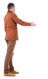 Back view of businessman in  movement reaches out to shake hands Stock Photo