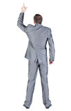 Back view of businessman pointing at wall. Royalty Free Stock Image