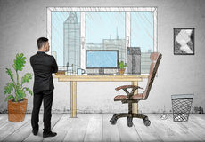 Back view of a businessman standing in hand drawn office looking out the window Royalty Free Stock Photo