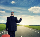 Back view of businessman with suitcase. On the road Stock Image