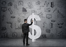 Back view of businessman touching big concrete dollar sign on the backgound with business doodles Royalty Free Stock Photo