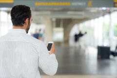 Back view of a of businessman using mobile smartphone. Royalty Free Stock Photo