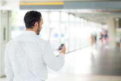 Back view of a of businessman using mobile smartphone. Stock Image