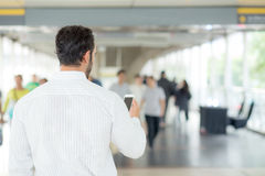 Back view of a of businessman using mobile smartphone. Royalty Free Stock Photography