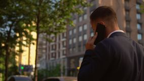 Male has conversation by mobile in town. Back view businessman walking down the street talking by phone, elegant man has phone negotiation outdoors. entrepreneur stock video