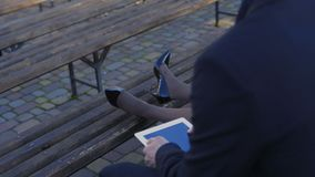 Back view. Businesswoman put her tiret legs on the bench. Shot in 4k stock footage