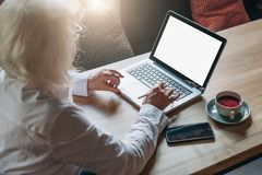 Back view. Businesswoman retired sitting in cafe at table, working on laptop. Telework, online education, e-learning. Back view. Business woman of middle age Royalty Free Stock Photos