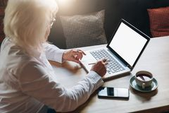 Back view. Businesswoman retired sitting in cafe at table, working on laptop. Telework, online education, e-learning. Back view. Business woman of middle age Stock Image