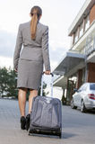 Back view of businesswoman walking suitcase on driveway Royalty Free Stock Photos