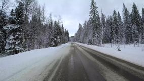 Back view from car mounted camera when vehicle driving winter snowy forest road. Video 4k.  stock video