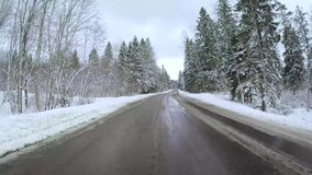 Back view from car mounted camera when vehicle driving winter snowy forest road. Video 4k.  stock footage