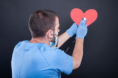 Back view of cardiologist using stethoscope on red shape heart Royalty Free Stock Photo
