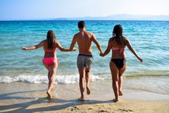 Back view of carefree friends holding hands and running into sea. royalty free stock photo