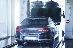 Back view of a carwash cleaning a car with rotating brushes royalty free stock photo