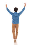 Back view of a casual man celebrating victory and walking. Back view of a casual man celebrating victory with hands up in the air , walking  on white background Royalty Free Stock Photo