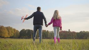 Back view of a caucasian man holding hand of teen blonde girl and pink toy airplane. Father walking with his adorable. Daughter in the autumn evening on the stock footage