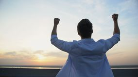 Back view of Caucasian man raising hands to sky on sunset background, motivation