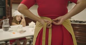 Back view of Caucasian woman in red dress tying apron. Blurred little girl sitting at the table at background and stock video footage